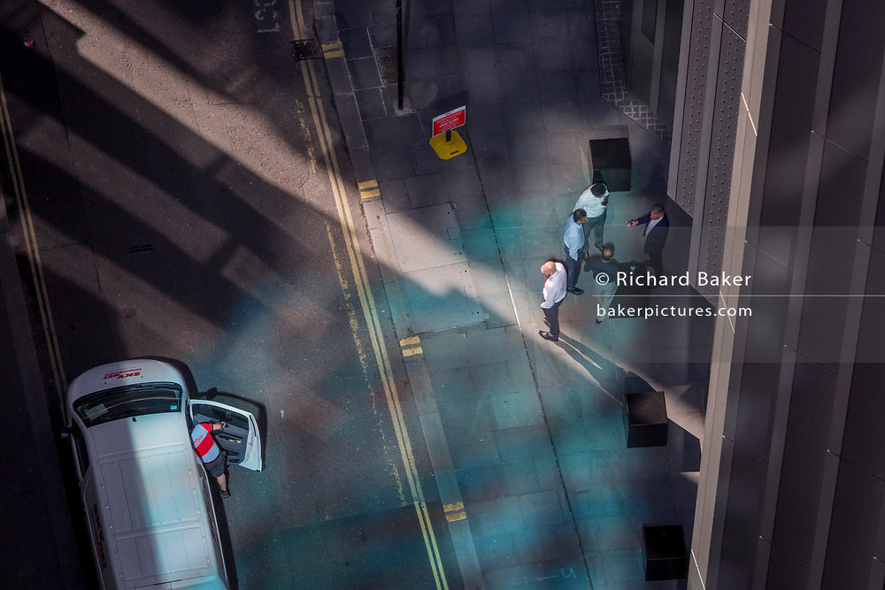Looking down from an aerial view towards a courier driver and small business figures walking through blue reflected light in the City of London, the capital's ancient financial district, on 13th May, in London, England.