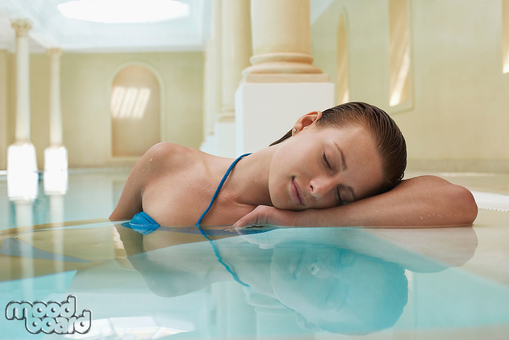 Young woman with eyes closed leaning on edge of swimming pool portrait