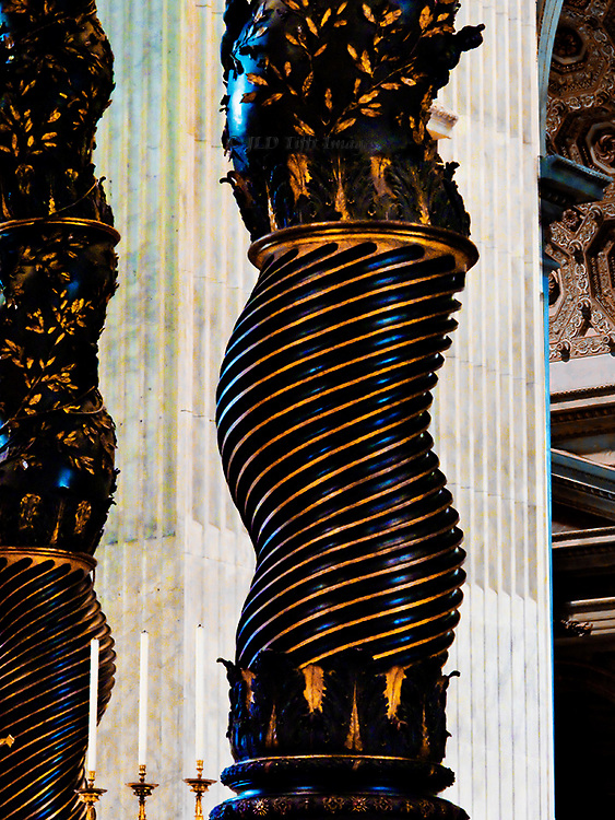 Detail of a twisted column of Bernini's baldachino in St. Peter's Basilica, Rome.  The black column with its gold ornamen tation is set against on e of the white marble square pillars in the basilica.  Three candles, unlit, in the foreground.