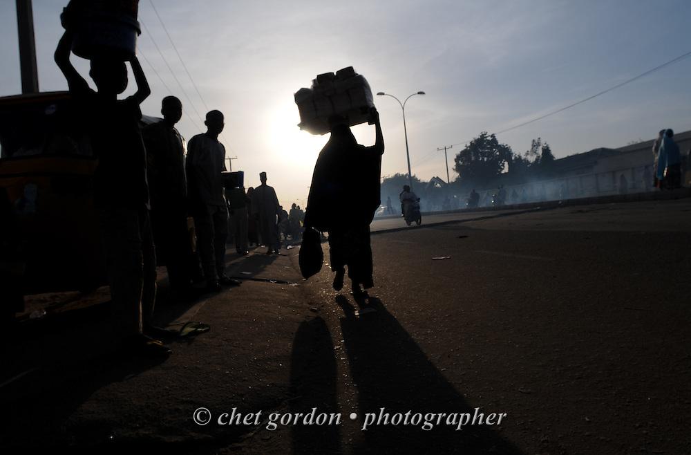 KANO, NIGERIA.  Pedestrians and street vendors move along a busy street in Kano, Nigeria on Thursday evening, December 6, 2012.