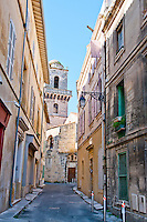 Quiet alleyway leading to a church in the historic city of Arles, France.