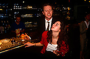 A young girl is groped on the breast by an amorous male acquaintance during an after-work party in the City of London. The couple have been drinking at the bar of this city club - the male holds a glass in one hand and the women's boob in the other which she doesn't appear to mind too much - consenting to the sexual harassment,