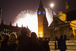 © Licensed to London News Pictures. 01/01/2016. London, UK. People in Parliament Square celebrate as they watch fireworks explode behind Big Ben to mark the start of the New Year, 2016 Photo credit : Vickie Flores/LNP