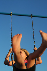 Barefoot child swinging against blue sky