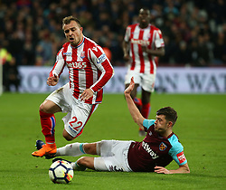 April 16, 2018 - London, England, United Kingdom - Stoke City's Xherdan Shaqiri gets tackles by West Ham United's Aaron Cresswell.during English Premier League match between West Ham United and Stoke City at London stadium, London, England on 16 April 2018. (Credit Image: © Kieran Galvin/NurPhoto via ZUMA Press)