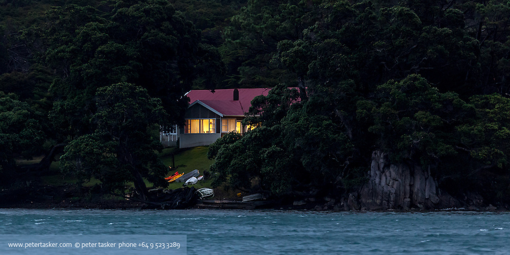 A bush surrounded house on the shore of Tryphena Harbour at dusk.