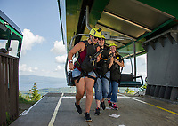 Mindy Hurd helps her mother Stephanie Hurd and Renee Charlifour off the Panorama lift at the top of Gunstock to begin their zipline experience with the Future In Sight group Thursday afternoon.  (Karen Bobotas/for the Laconia Daily Sun)