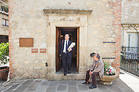 GANGI, ITALY - 30 MAY 2015: Mayor of Gangi Giuseppe Ferrarello steps out of Palazzo Bongiorno in Gangi, Italy, on May 30th 2015. Gangi is a town with a population of 7,000 between Palermo and Catania, in the centre of Sicily, whose local administration is giving away abandoned houses of the historical centre for free. The Mayor of Gangi Giuseppe Ferrarello conceived the initiative of giving houses for free as a means to diversify the local economy - primarily dependent on agriculture and animal husbandry - by boosting tourism-related activities, and consequently counteract the phenomenon of depopulation that is typical of many small Italian towns where employment possibilities have been on a downward trajectory for years. The renovations of the assigned homes have also given work to local artisans.