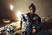 (MODEL RELEASED IMAGE). On Sunday, ignoring a half-eaten tomato in her henna-stained hand, 18-year-old Pai somberly contemplates what she has just learned: later today she will formally wed her first cousin, Baba Nientao, and then move to his home in Ivory Coast. None of the parents attend the ceremony. Instead, Pai's girlfriends raucously lead her (hidden under a shawl) to the Town Hall, where she and Baba sign their marriage license alone with the mayor. Hungry Planet: What the World Eats (p. 214). The Natomo family of Kouakourou, Mali, is one of the thirty families featured, with a weeks' worth of food, in the book Hungry Planet: What the World Eats.