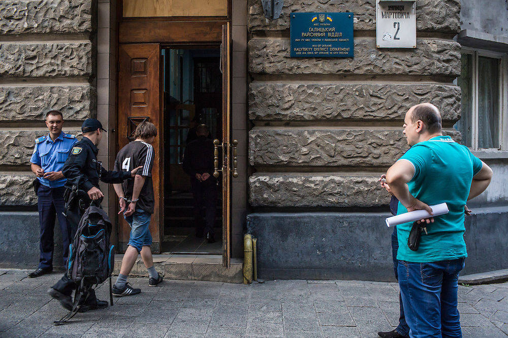 LVIV, UKRAINE - SEPTEMBER 16, 2015: A member of the new Lviv police takes Vladimir, 26, into a police station for processing by members of the old police force after he was found intoxicated and sleeping in the city's central square and then swore at police officers in Lviv, Ukraine. In an effort to reform the notoriously corrupt Ukrainian police force, an entirely new force has been established in several cities, including Kiev and Lviv, with a primary focus on patrolling the streets. CREDIT: Brendan Hoffman for The New York Times