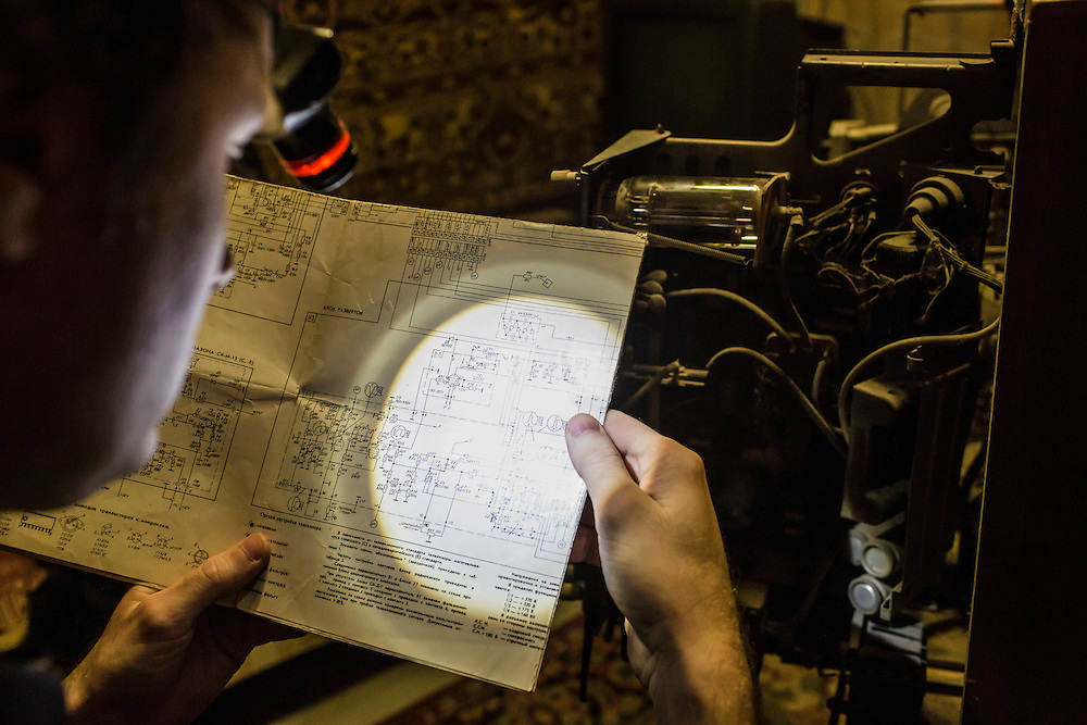 LUHANSK, UKRAINE - MARCH 15, 2015: Aleksandr Kryukov looks at diagrams of circuits for an old Soviet television he is trying to repair in Luhansk, Ukraine. CREDIT: Brendan Hoffman for The New York Times