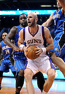 Dec. 09, 2012; Phoenix, AZ, USA; Phoenix Suns center Marcin Gortat (4) looks to make a pass during the game against the Orlando Magic forward Glen Davis (11) and center Nikola Vucevic (9) in the second half at US Airways Center. The Magic defeated the Suns 98-90. Mandatory Credit: Jennifer Stewart-USA TODAY Sports