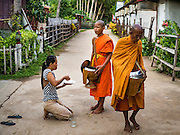 "20 JUNE 2016 - DON KHONE, CHAMPASAK, LAOS: A woman makes an offering to monks from Wat Khone Nua on their morning alms' rounds, called the ""tak bat"" in Don Khone village on Don Khone Island. Don Khone Island, one of the larger islands in the 4,000 Islands chain on the Mekong River in southern Laos. The island has become a backpacker hot spot, there are lots of guest houses and small restaurants on the north end of the island.     PHOTO BY JACK KURTZ"