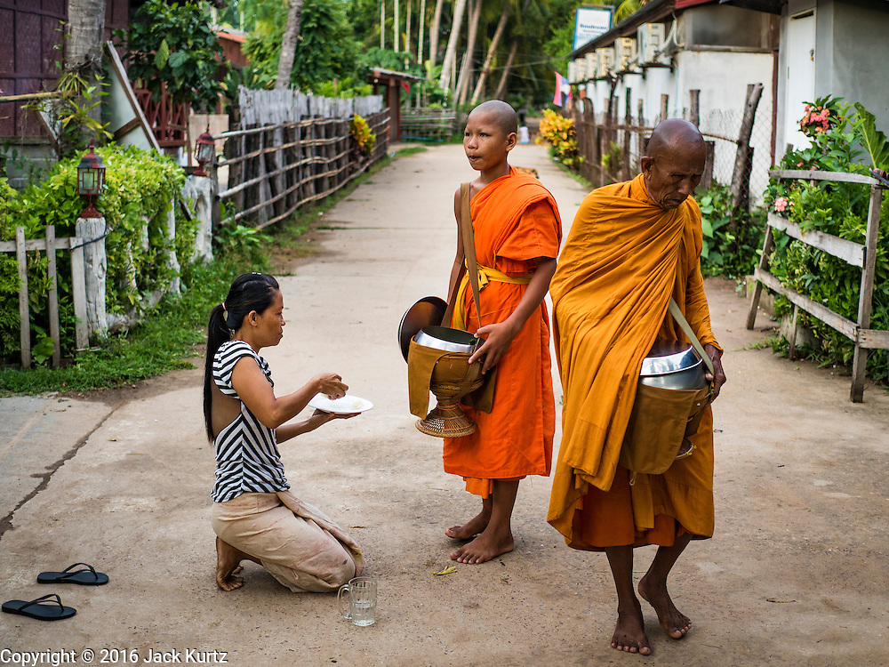 """20 JUNE 2016 - DON KHONE, CHAMPASAK, LAOS: A woman makes an offering to monks from Wat Khone Nua on their morning alms' rounds, called the """"tak bat"""" in Don Khone village on Don Khone Island. Don Khone Island, one of the larger islands in the 4,000 Islands chain on the Mekong River in southern Laos. The island has become a backpacker hot spot, there are lots of guest houses and small restaurants on the north end of the island.     PHOTO BY JACK KURTZ"""