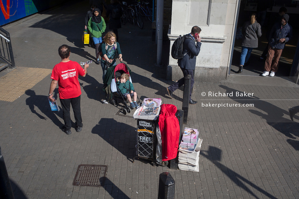 A man wearing a red t-shirt hands out free copies of the Evening Standard newspaper and an accompanying ES Magazine to passers-by and pedestrians at Vauxhall station, on 11th Arpil 2019, in south London, England.