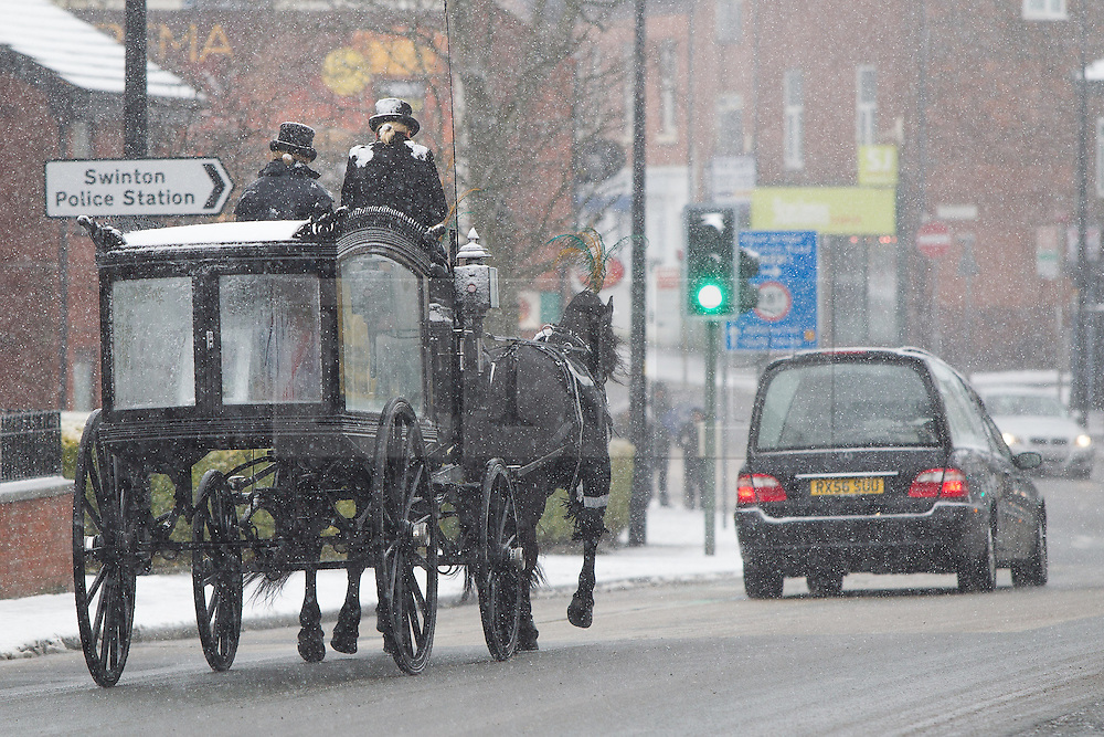 © Licensed to London News Pictures . 05/02/2013 . A horse drawn funeral cortege in Swinton, Manchester , the horse drivers in snow-capped top hats and tails . Manchester , UK . Heavy snow is causing traffic delays and accidents on the roads in and around Manchester . Photo credit : Joel Goodman/LNP