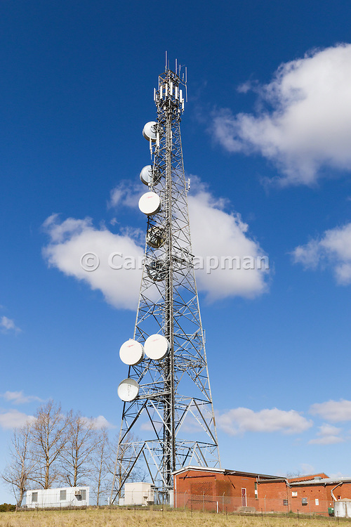 Urban provincial  cellular, microwave and telecom communications systems lattice tower under blue sky with cumulus cloud in Orange, New South Wales, Australia.
