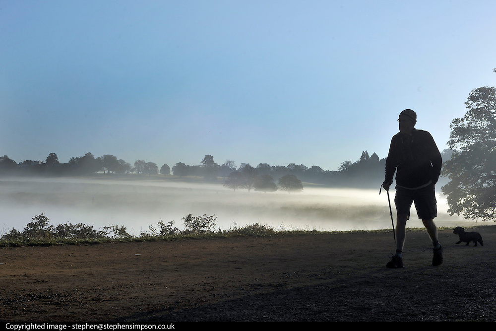 © Licensed to London News Pictures. 15/10/2011. Richmond, UK. A walker in the early morning mist. Early morning in Richmond Park, Surrey today 15 October 2011. Temperatures are set to fall across the UK in the coming week as Autumn takes hold. Photo: Stephen Simpson/LNP