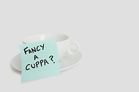 Close-up of sticky notepad stuck to empty coffee cup over white background