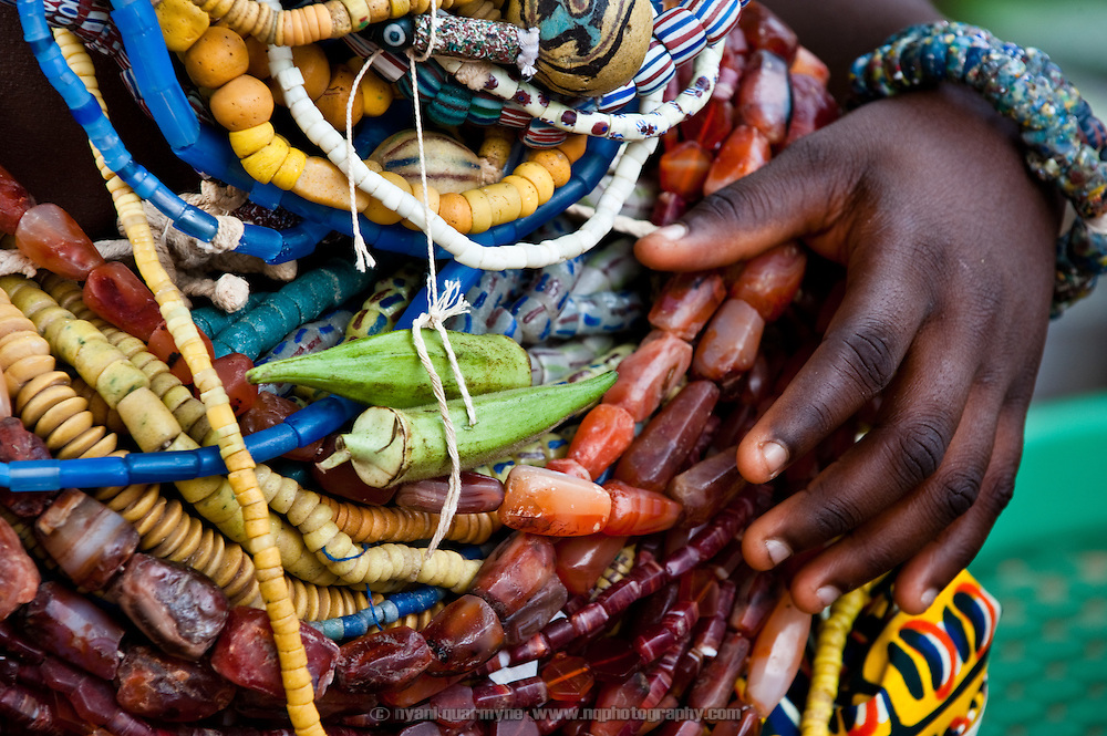 A Dipo-Yo (adolescent girl undergoing Dipo) wears okra fingers amongst her beads in tribute to her late mother, who was a vegetable seller. Beads are a form of wealth, handed down from mother to daughter through the generations, and each design has a particular significance. During Dipo, the number of beads worn by a girl is indicative of her family's wealth, as well as the strength of her relationship with them - if she is seen to be respectful older relatives will pitch in and lend her their beads.