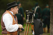A photographer wearing period dress prepares to take a picture the 124th New York State Volunteers and their families during a Civil War reenactment at the Orange County Farmers Museum on Sept. 23, 2006. The photographer is holding a modern camera he also used.