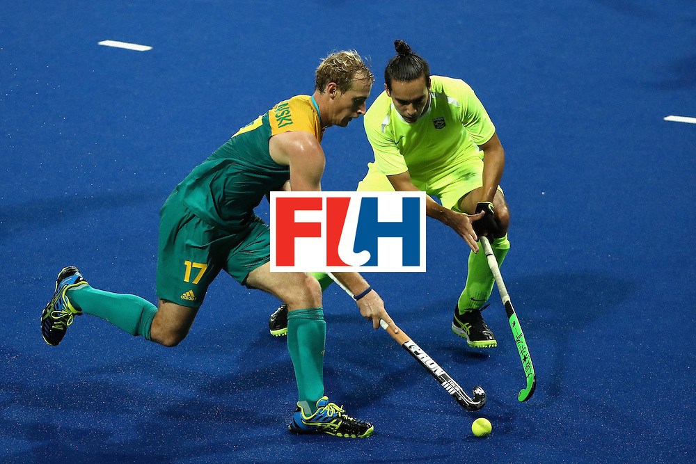 RIO DE JANEIRO, BRAZIL - AUGUST 12:  Aran Zalewski #17 of Australia runs past Patrick van der Heijden #15 of Brazil during a Men's Preliminary Pool B match on Day 7 of the Rio 2016 Olympic Games at the Olympic Hockey Centre on August 12, 2016 in Rio de Janeiro, Brazil.  (Photo by Sean M. Haffey/Getty Images)