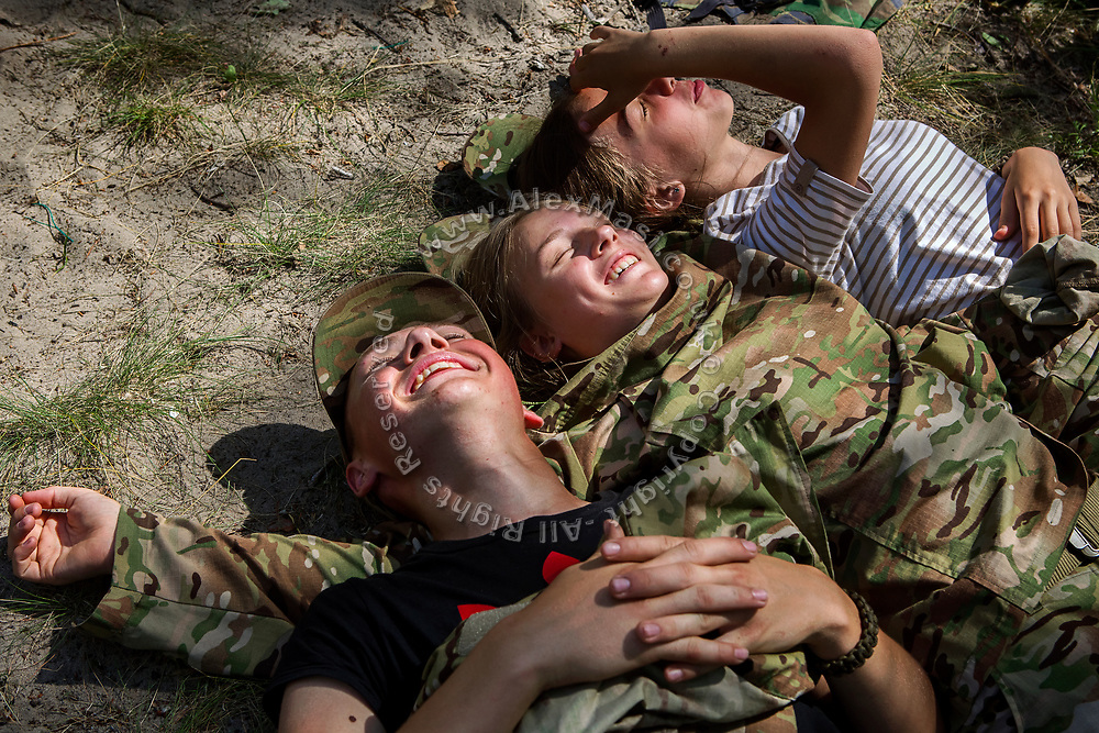 Youngsters participating to the ultra-nationalistic Azovets children's camp are having fun sunbathing on the grass, after tactical training on the banks of the Dnieper river, in Kiev, Ukraine's capital.