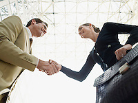 Businessman and businesswoman shaking hands (low angle view)