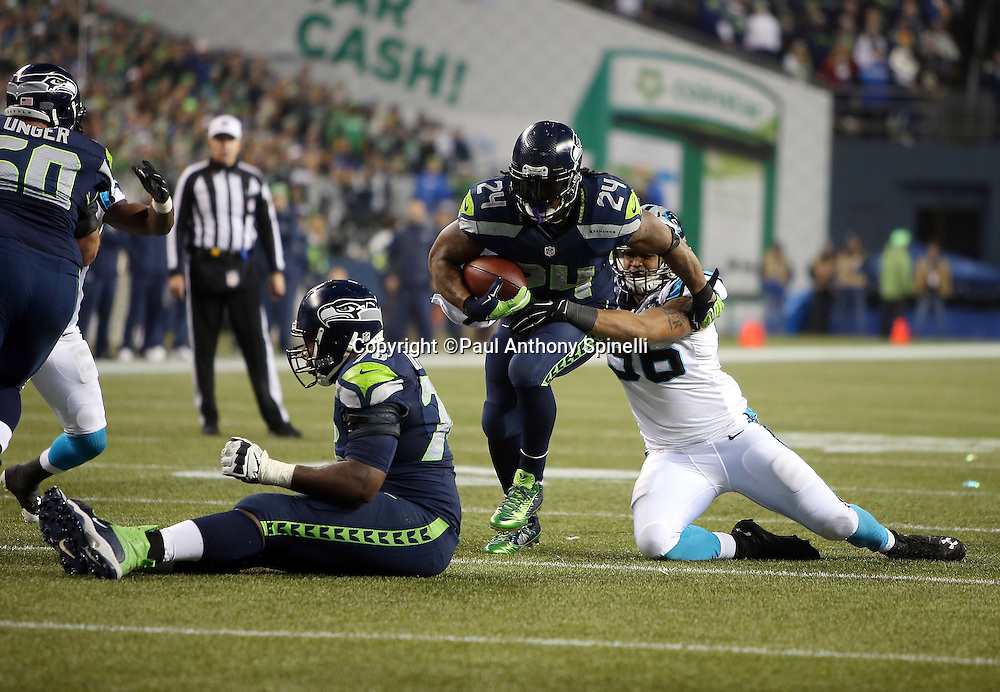 Seattle Seahawks running back Marshawn Lynch (24) breaks away from a tackle attempt by Carolina Panthers defensive end Wes Horton (96) as he runs the ball in the third quarter during the NFL week 19 NFC Divisional Playoff football game against the Carolina Panthers on Saturday, Jan. 10, 2015 in Seattle. The Seahawks won the game 31-17. ©Paul Anthony Spinelli