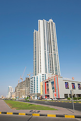 View of street and high-rise Corniche Tower along Corniche in Ajman emirate in United Arab Emirates