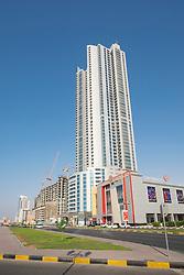 View of street and high-rise Corniche Tower along Corniche in Ajman emirate in United Arab Emirates