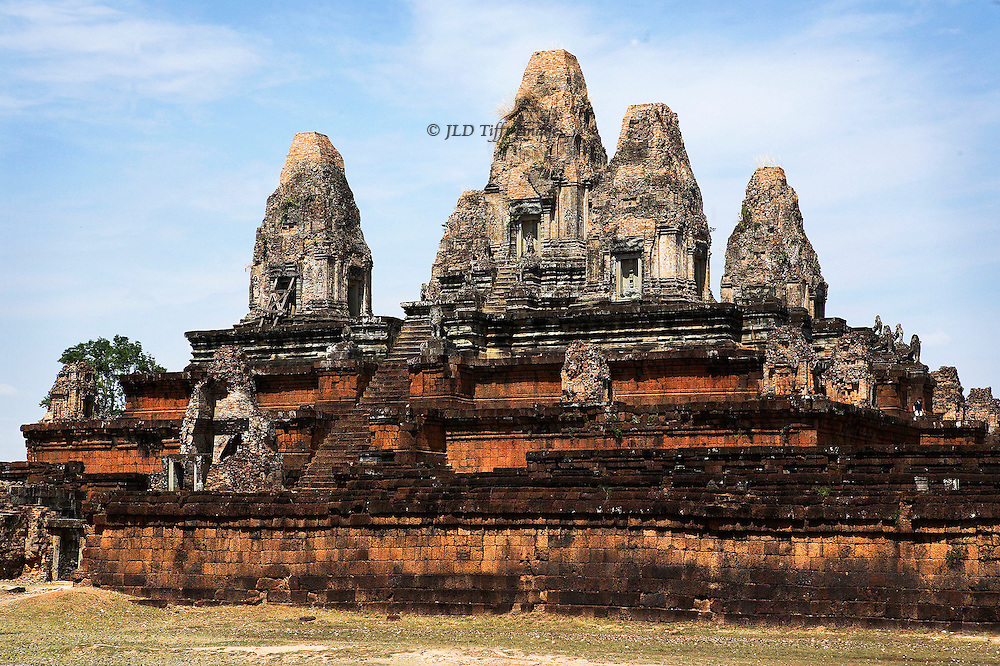 Bakong, near the town of Roluos, is the oldest temple in the Angkor Archaeological Park (9th century).  View of the central pyramid of five levels, of brick and sandstone, reconstructed during the 1930s from original building parts.  The pyramid symbolizes Mount Meru of Hindu cosmology.