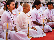 "22 FEBRUARY 2016 - KHLONG LUANG, PATHUM THANI, THAILAND:  People pray during the Makha Bucha Day service at Wat Phra Dhammakaya.  Makha Bucha Day is a public holiday in Cambodia, Laos, Myanmar and Thailand. Many people go to the temple to perform merit-making activities on Makha Bucha Day, which marks four important events in Buddhism: 1,250 disciples came to see the Buddha without being summoned, all of them were Arhantas, Enlightened Ones, and all were ordained by the Buddha himself. The Buddha gave those Arhantas the principles of Buddhism, called ""The ovadhapatimokha"". Those principles are:  1) To cease from all evil, 2) To do what is good, 3) To cleanse one's mind. The Buddha delivered an important sermon on that day which laid down the principles of the Buddhist teachings. In Thailand, this teaching has been dubbed the ""Heart of Buddhism."" Wat Phra Dhammakaya is the center of the Dhammakaya Movement, a Buddhist sect founded in the 1970s and led by Phra Dhammachayo.     PHOTO BY JACK KURTZ"