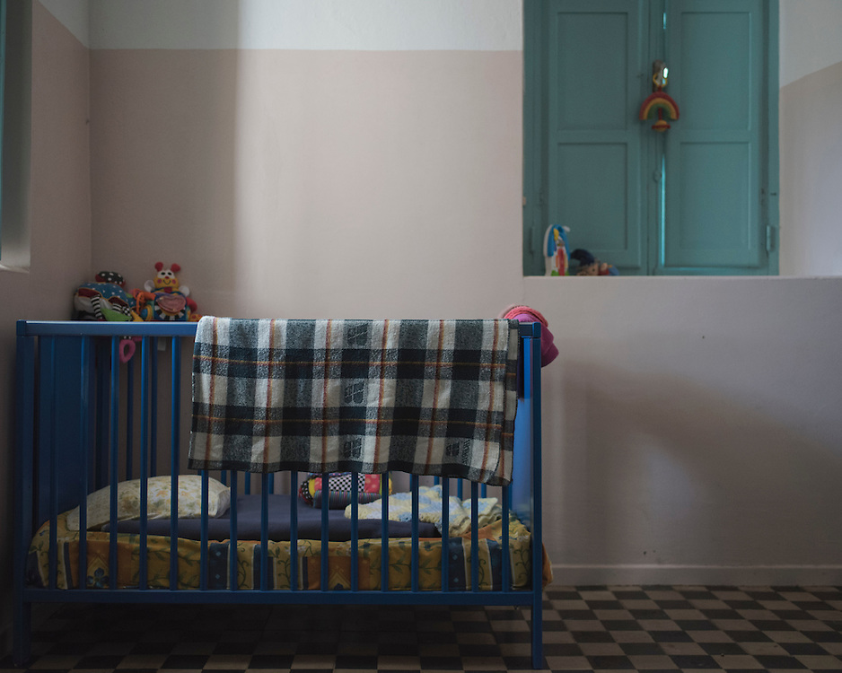 A child's cot and toys in Villa Artemis, a shelter for 30 refugee women and their children in the grounds of Leros Hospital.<br />