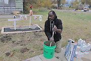 Clinton mixes concrete as he builds a memorial with crosses in front of the abandoned home where the body <br /> of his girlfriend was found.