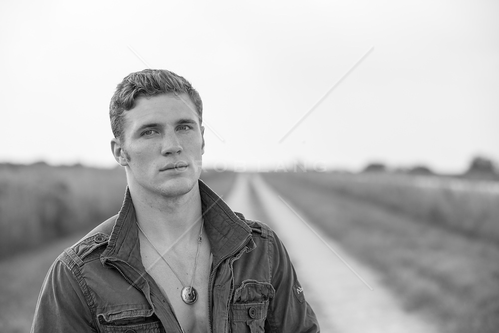 portrait of a handsome All American man on a dirt road
