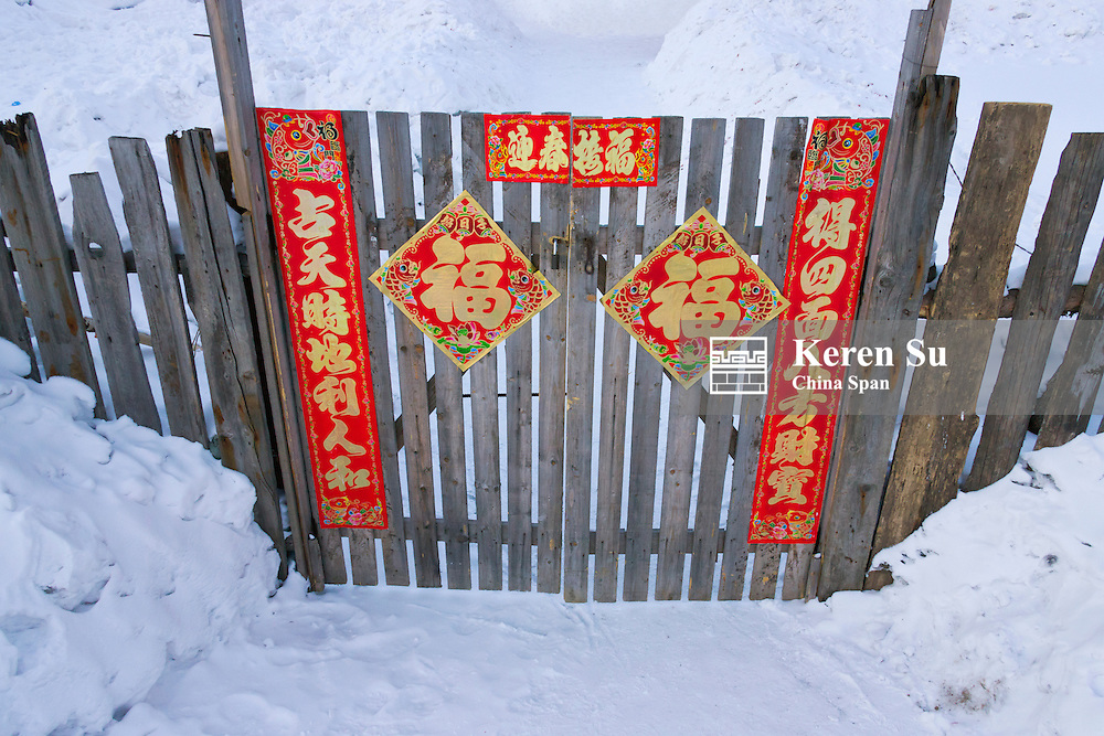 Village house fence decorated with red posters during Chinese New Year, Snow Village, Heilongjiang Province, China