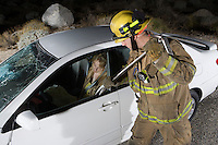 Firefighter rescuing car accident victim