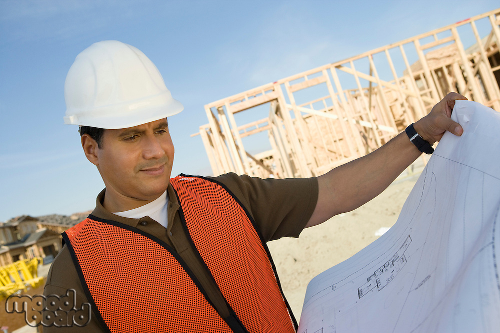 Construction worker standing on construction site and holding blueprints