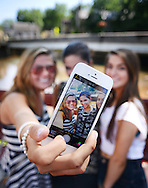 NEW HOPE, PA - JUNE 02:  From left, Allie Becker, 19, Lauren Fitzpatrick, 18 and Capri Wagner, 18 all of Newtown, Pennsylvania are seen through an iPhone monitor as they make a selfie near the Bucks County Theater on a warm afternoon June 2, 2014 in New Hope, Pennsylvania.  The temperature reached 82 degrees in New Hope and is expected to remain in the mid-80's for the next few days. (Photo by William Thomas Cain/Cain Images)