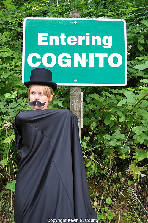 "Humorous photograph of a woman dressed as a villan standing next to a sign that reads ""ENTERING COGNITO"" visually depicting the expression ""How long will you be incognito?"""