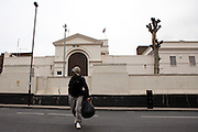 An ex-prisoner leaving HMP Pentonville with his posessions in a prison issue holdall and a black plastic binbag.
