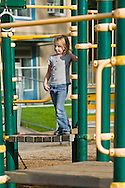 blonde girl, caucasian, standing on play equipment at a park or school