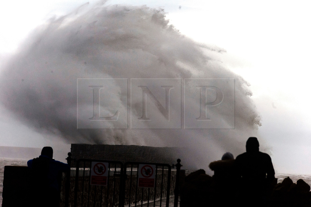 © Licensed to London News Pictures. 09/02/2020. Porthcawl, Bridgend, Wales, UK.  Massive waves and gale force wind pound the harbour wall  at dawn in the Welsh seaside resort of Porthcawl in Bridgend, UK. Photo credit: Graham M. Lawrence/LNP