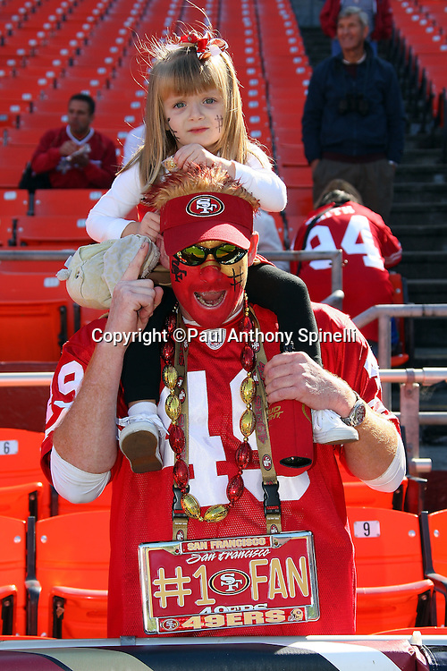 A San Francisco 49ers fan with a painted face and what appears to be his young daughter on his shoulders pose for a photo before the NFL football game against the Tennessee Titans, November 8, 2009 in San Francisco, California. The Titans won the game 34-27. (©Paul Anthony Spinelli)