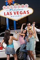 "Young woman photographing two friends with Elvis impersonator, ""Welcome to fabulous Las Vegas"" sign in background, Las Vegas, Nevada, USA"