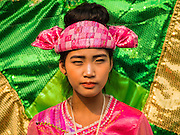 "05 APRIL 2015 - CHIANG MAI, CHIANG MAI, THAILAND: A Tai Yai woman dressed as a pea fowl, the national symbol of Myanmar (Burma) during the second day of the three day long Poi Song Long Festival in Chiang Mai. The Poi Sang Long Festival (also called Poy Sang Long) is an ordination ceremony for Tai (also and commonly called Shan, though they prefer Tai) boys in the Shan State of Myanmar (Burma) and in Shan communities in western Thailand. Most Tai boys go into the monastery as novice monks at some point between the ages of seven and fourteen. This year seven boys were ordained at the Poi Sang Long ceremony at Wat Pa Pao in Chiang Mai. Poy Song Long is Tai (Shan) for ""Festival of the Jewel (or Crystal) Sons.    PHOTO BY JACK KURTZ"