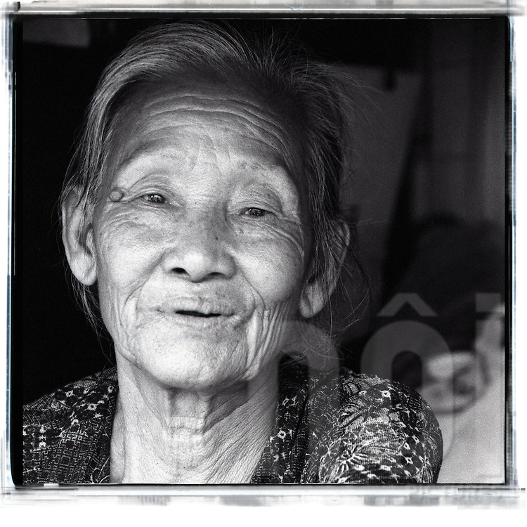 Black and white picture of an old vietnamese woman living along the railway of Hanoi.