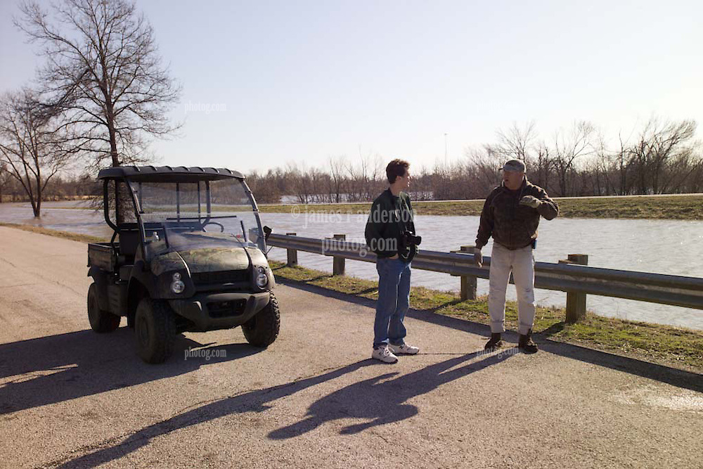Pete Greeley, traveler, and John North, local resident, discussing the Bush Creek Marsh Arch Rainbow Bridge on Old Route 66 Riverton, KS as the area ia hit by a 100 year flood.