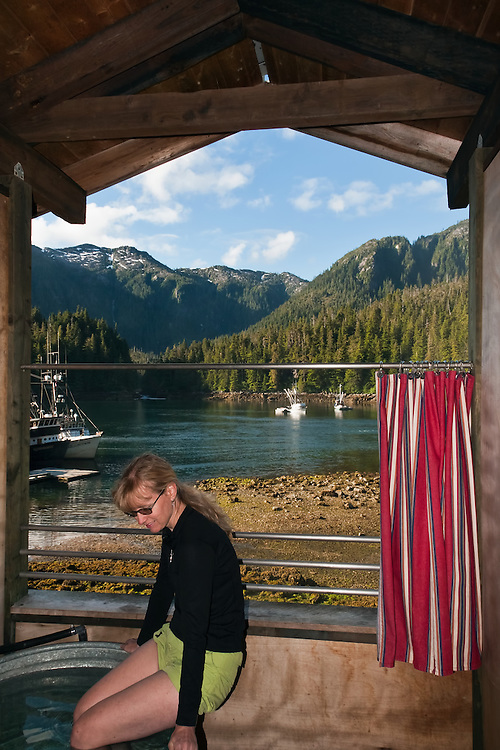 A bather tests the hot spring water in a bath house at Baranof Hot Springs with the harbor and coastal mountains in the background in the Inside Passage of Southeast Alaska. Summer. Morning. MR.